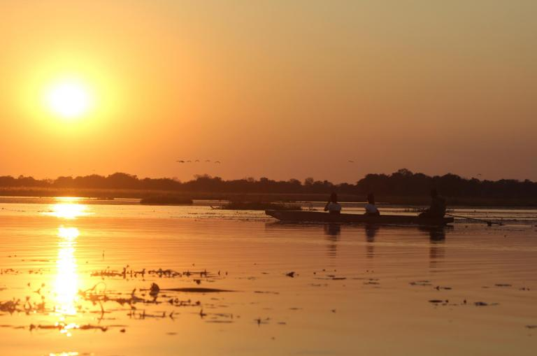 Fahrt im Mokorokoro Einbaum auf dem Sambesi River im Sonnenuntergang während der 18-tägigen Botswana-Simbabwe Safari