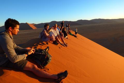 Reisegruppe der Rundreise auf der Düne Sossuvlei in der Namib Wüste
