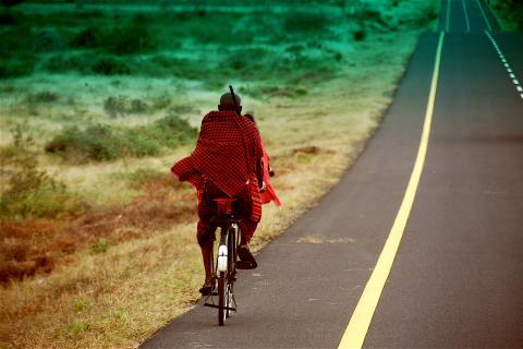 Impressionen der Ostafrika Rundreise: Masai Krieger auf dem Fahrrad auf einer Straße durch den Masai Mara Nationalpark in Kenia