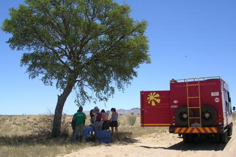 Während der Rundreise durch das südliche Afrika: Südafrika, Namibia, Botswana und Simbawe stehen auf dem Programm. Mittagspause & Lunch neben dem Safari Truck im Schatten der afrikanischen Sonne