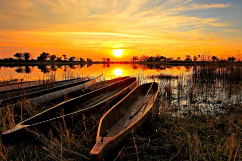 Sonnenununtergang mit Mokoroko im Okavango Delta in Botswana