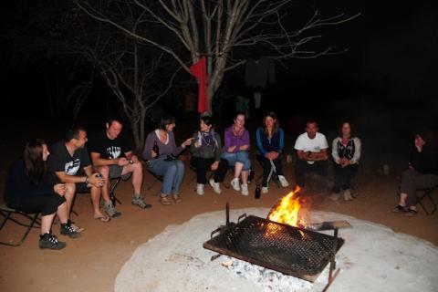 Safari Reisegruppe beim gemütlichen Zusammensitzen rund um das Lagerfeuer in Gwabi / Zimbabwe