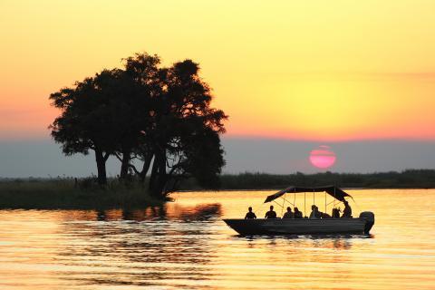 Sundowner auf dem Chobe River. Bei Sonnenuntergang mit dem Boot über den Chobe Fluss in Botswana fahren