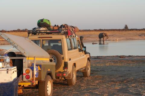Sunway Safari Truck am Wasserloch mit Elefant im Hwange National Park