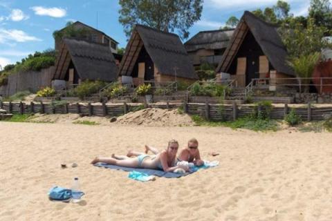 Entspannte Urlauber am Traumstrand von Vilanculos mit Hütten im Hintergrund