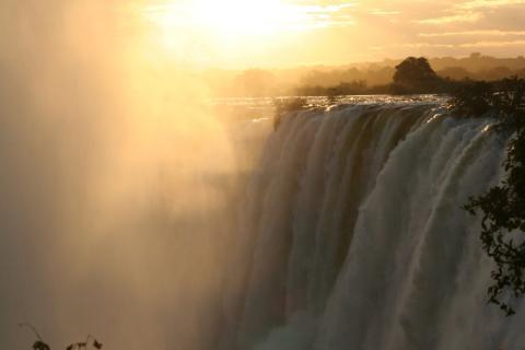 Sonnenuntergang an den Victoria Fällen in Simbabwe: Die Sonne strahlt in der aufsteiegenden Gischt