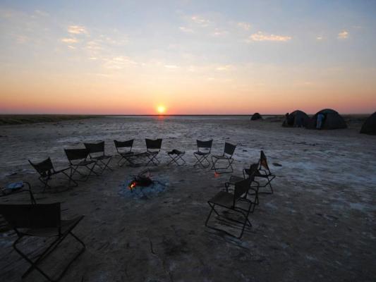 Sonnenaufgang in den Makgadikgadi-Salzpfannen: Camp mit Lagerfeuer