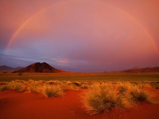 Regenbogen und Sonnenuntergang über der Namibwüste in Namibia