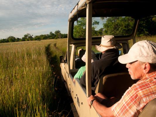 Reisende im offenen Sunway Safari Jeep auf der Fahrt durchs hohe Gras